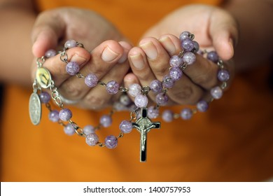 Rosary in hand. Young junior lady holding rosary with open hand. Female hands holding a rosary with Jesus Christ Cross Crucifix. Month of Rosary, Christian Catholic religious symbol of faith concept.