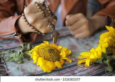Rosary in hand. Young junior lady holding rosary tightly. Female hands holding a rosary with Jesus Christ Cross Crucifix. Christian Catholic religious symbol of faith concept on messy table background