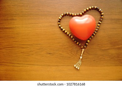 Rosary with heart shape on wood table. Tiger's eye stone rosary for prayer. Copy space. Muslim.