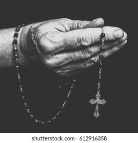Rosary in old closed hand. Black and white photography