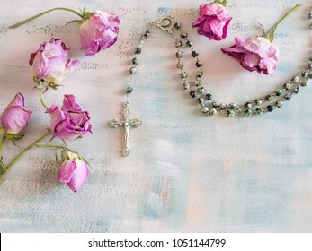 rosary on a painted pastel colored background with dry roses