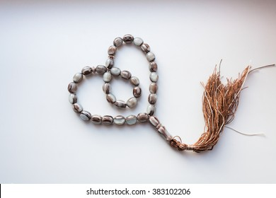 "rosary on a white background and the Koran . In the book it is written "" Koran """