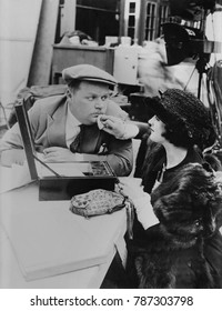Roscoe Fatty Arbuckle, American actor, getting touch up by make up girl on movie set, c. 1920. Arbuckle was one of the most popular silent stars of the 1910s. In 1920 He signed a contract with Paramou