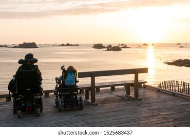 Roscoff, Finistere / France - 21 August 2019: two people in wheelchairs enjoy the opportunity to watch a sunset over the beach and ocean
