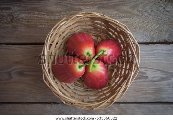Rose apple in basket on wood table.