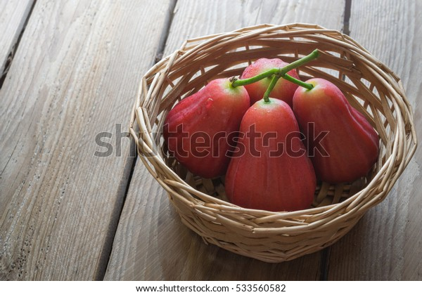 Rose apple in basket on wood table.