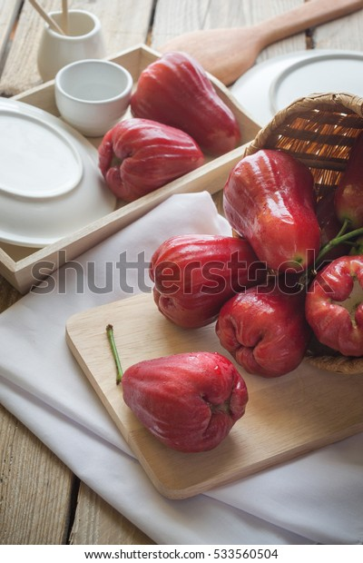 Rose apple in basket pouring rose apple into a wooden board on wood table.