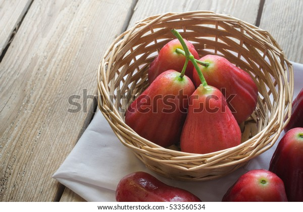 Rose apple in basket with white fabric on wood table.