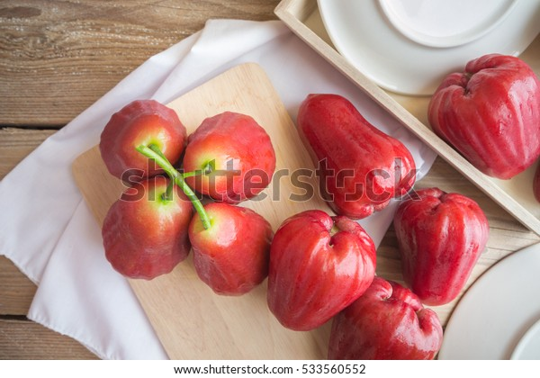Rose apple with wooden board on wood table.