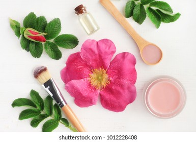 Rose aroma cosmetic products for natural beauty treatment. Fresh pink flower, green leaves, essential oils, skincare mask, top view botanical spa background.