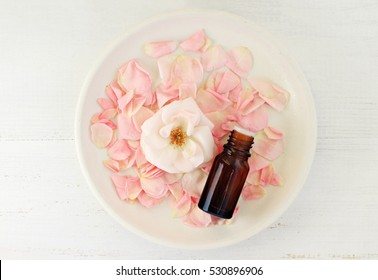 Rose aromatherapy oil. Dropper bottle on ceramic plate with tender pink petals and flower, center on wooden table, top view. Soft focus. Homemade Healing Lotion Recipe