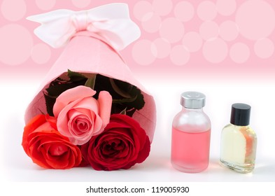 Rose bouquet and essential oil in front of pink blur