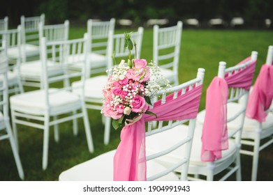 rose bouquet and pink textile on white chair at wedding place