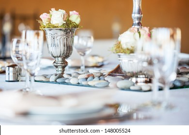 Rose bouquet in silver vase on decorated table at wedding reception