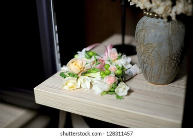 rose boutonnieres on shelf at home