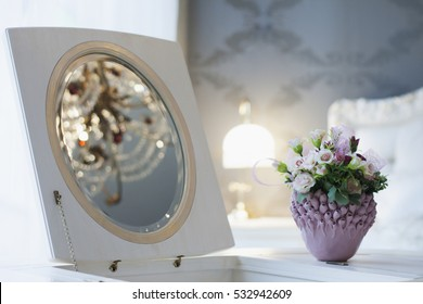 The rose bowl in the bedroom on a table near the mirror.
