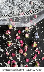 rose buds and rice with lace cloth on black background - wedding tradition