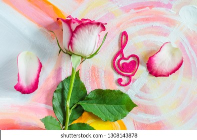 Rose with a decorative heart in the shape of a treble clef with pink felt on the background of painting. Valentine's day, mother's day congratulation.