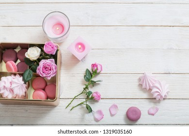 rose, desset and burning candles on white wooden background
