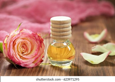 Rose essential oil in glass bottle on wooden background
