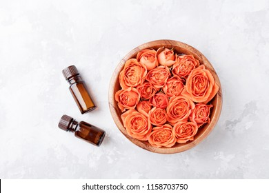 Rose flower in bowl and essential oil bottle on stone table top view. Spa, aromatherapy, wellness, beauty background.
