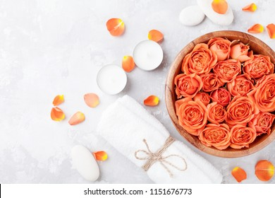 Rose flower in bowl, towel and candles on stone table top view. Spa, aromatherapy, wellness, beauty background.
