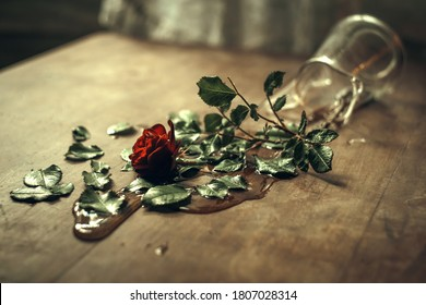 A rose flower fell from a vase on the table, spilling water.