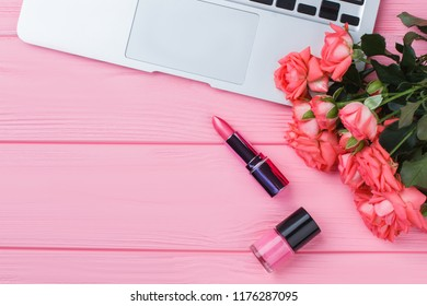 Rose flowers bouquet, lipstic, lacquer and laptop. Flat lay, top view. Pink wooden table surface.