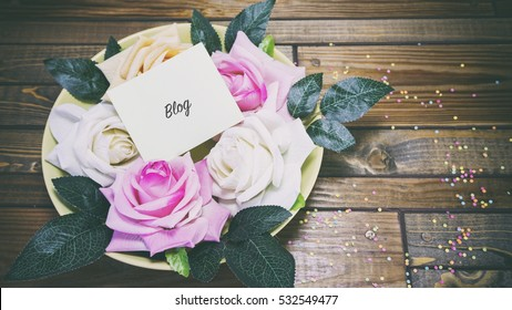 Rose flowers on a plate on a wooden table, a note on the paper blog