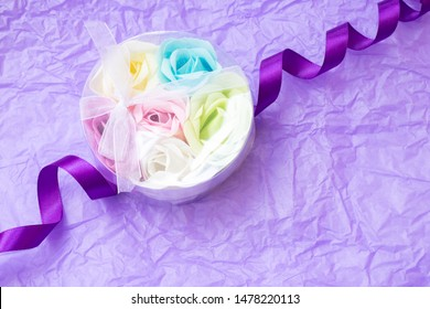 Rose flowers shaped scented soap petals in transperent round box on crimpled violet paper background. Handcrafted soap petals.