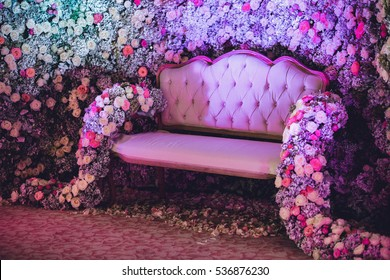 Rose garlands hang from white couch standing before wall of flowers