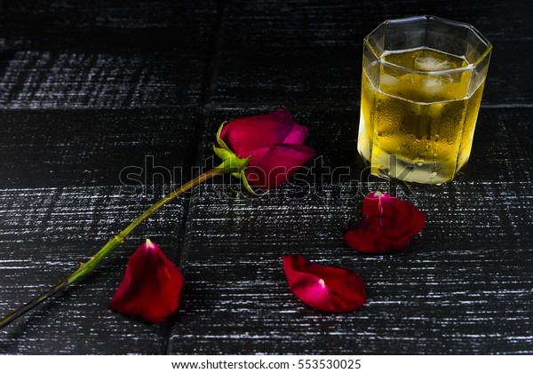 Rose and a glass of beer on wooden background
