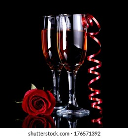 Rose with glasses and a red tape Alcohol and flower. Glasses with drink and a red rose.