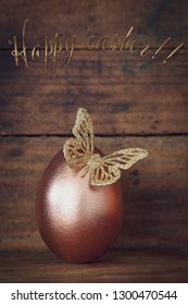 rose gold easter egg decorated with a golden glitter butterfly  and text happy easter before  old wooden background