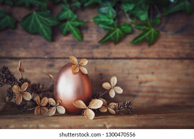 rose gold easter egg decorated with withered blossoms before  old wooden background and a twine of ivy