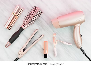 Rose gold hair care and beauty products on marble countertop