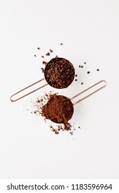 Rose gold measuring cups of cacao nips and cocoa powder on a white background, flat lay healthy food concept