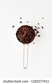 Rose gold measuring cups of cocao nips on a white background, healthy food concept