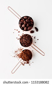 Rose gold measuring cups of cocoa beans, cacao nibs and cocoa power on a white background, flat lay healthy food concept
