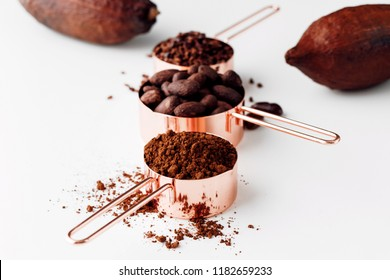 Rose gold measuring cups of cocoa beans, cacao nips, cocoa powder and cocoa pods on a white background, healthy food concept