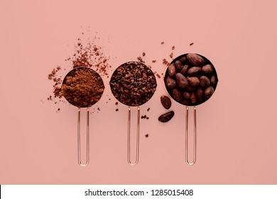 Rose gold measuring cups of cocoa beans, cacao nips and cocoa powder on a pink background, flat lay healthy food concept