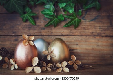 rose gold,gold and silver easter eggs decorated with withered blossoms before  old wooden background with twine of ivy