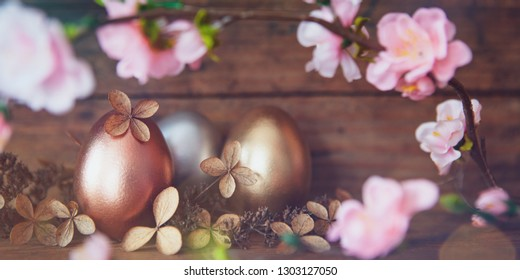 rose gold,gold and silver easter eggs decorated with withered blossoms before  old wooden background