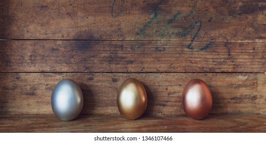 rose gold,gold and silver easter eggs on old wooden background