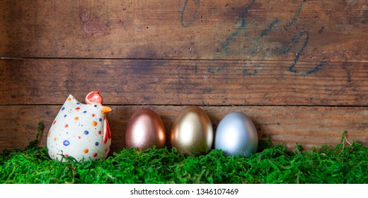 rose gold,gold and silver easter eggs and chicken in moss before  old wooden background