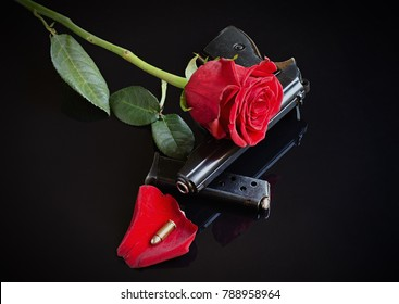 Rose, gun and bullet on black reflective background