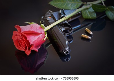 Rose, gun and two bullets on black reflective background