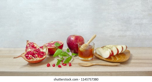 Rose Hashanah(jewish holiday)concept;.honey, apple and pomegranate on wooden floor have space for text.
