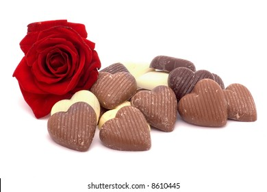 a rose and heart-shaped chocolates on white