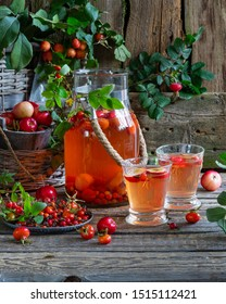 Rose hip and apple compote in glass jar and beakers on wooden board. Ripe red berries with leaves in plate and basket. Autumn harvesting season, fresh vitamins on gray background. Healthy nutrition